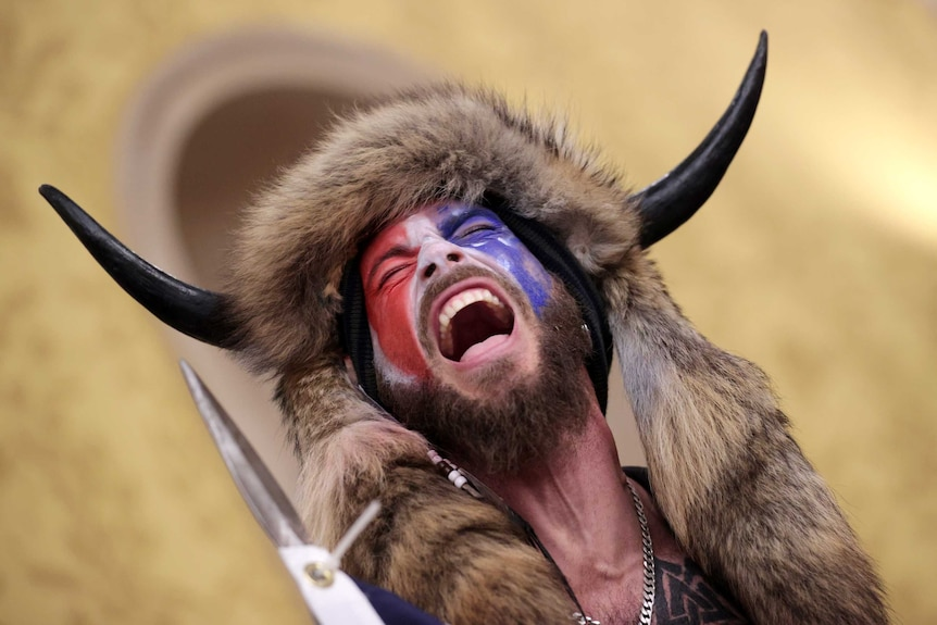 A man wearing a horned fur hat holding a spear yells inside the US Capitol Building while holding a spear.