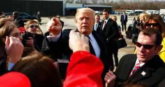 Donald Trump points as he is surrounding by a group of people.
