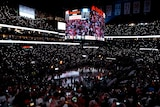 An NBA arena lies in near-darkness, as fans use lights from their mobile phones to see during a playoff game.