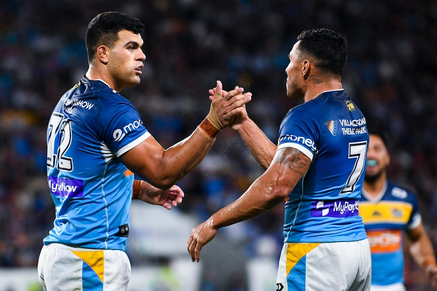 Two Gold Coast Titans NRL players shake hands as they celebrate a try.