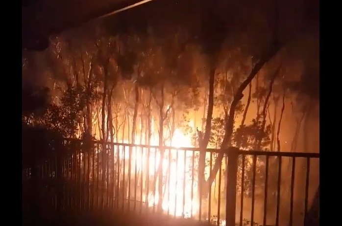 The orange glow of a bushfire can be seen behind the fence line of a home, burning through bushland.