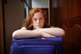 Headshot of teenager Adelaide Hardy leaning on a suitcase in her house.