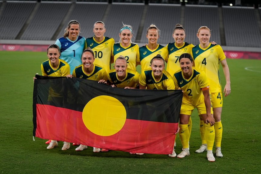Australia's women's football team, the Matildas, pose with the Aboriginal flag before their first game of the Tokyo Olympics.