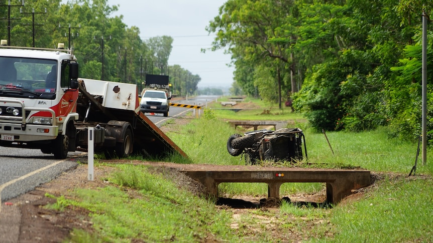 Emergency vehicles are by the edge of the road where a ATV is on its side.