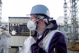 A man in a helmet, face mask and vest stands outside a nuclear plant