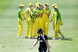 Australian players hug in a large group as a New Zealand player wearing black walks in the foreground