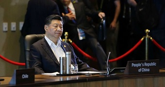 Xi Jinping sitting at the conference table at APEC.