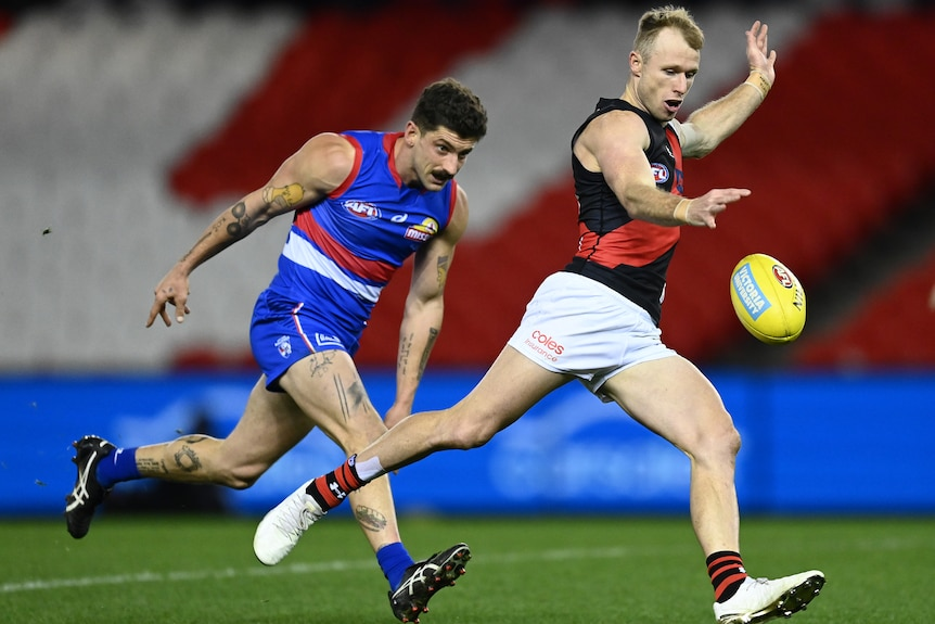An AFL player kicking the ball with his opponent behind him