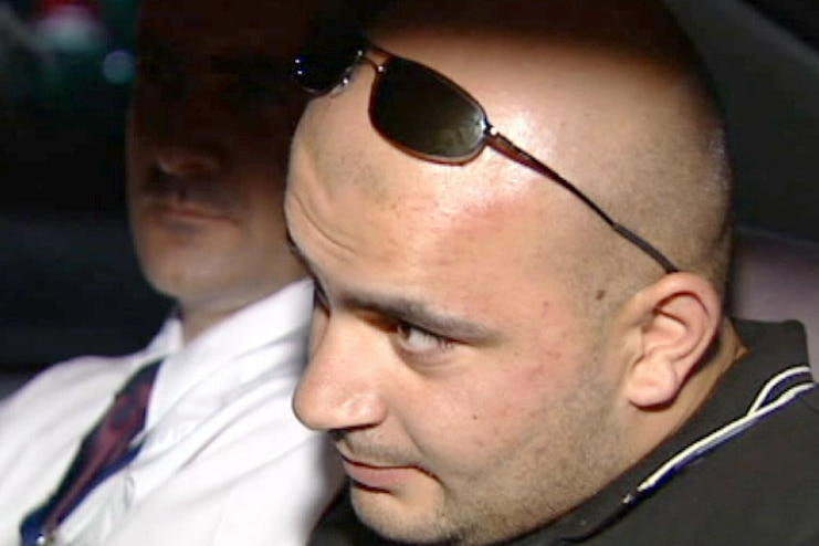 Hizir Ferman sits in a car with his sunglasses on his head. Another man in a tie and white shirt sits next to him.