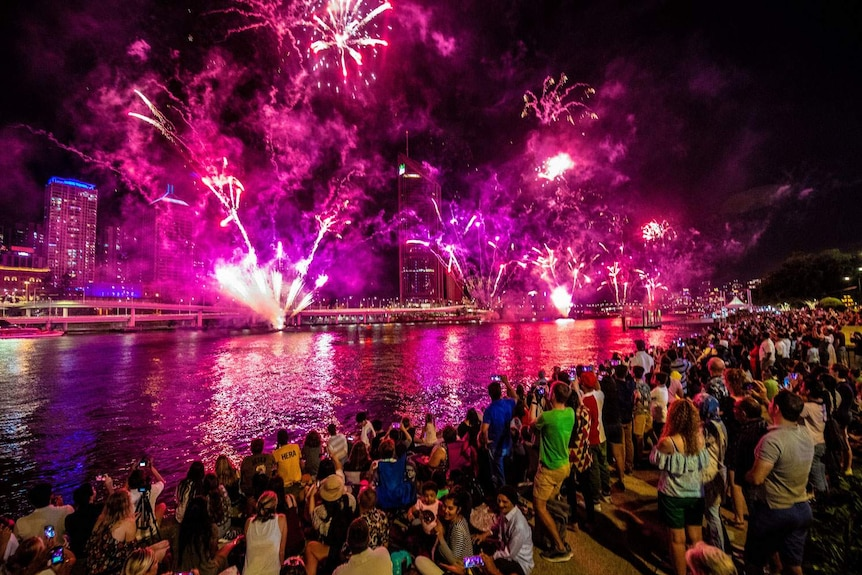 People watch fireworks on New Year's Eve over the Brisbane River at South Bank on December 31, 2018.