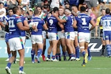 Players crowd around a tryscorer in a rugby league match in Auckland.