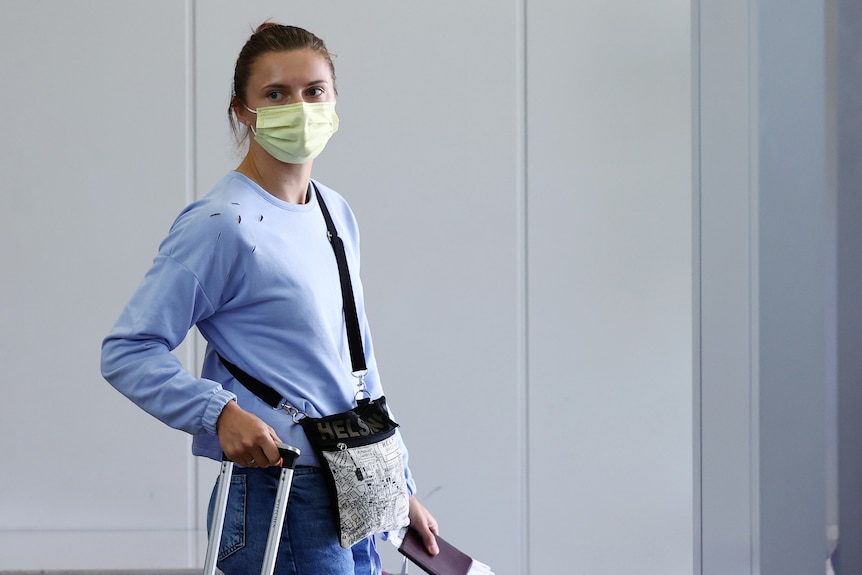 A woman looks sternly while wearing a facemask and carrying luggage at an airport