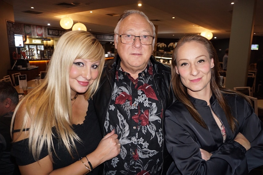 An elderly man with two women next to him