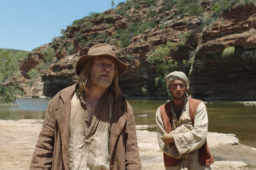 Two men stand in a gorge