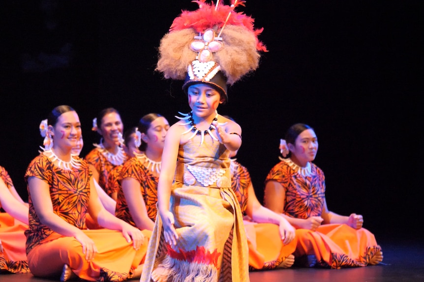 Young girl with traditional cloth mat dress and furry pink head dress performing on stage