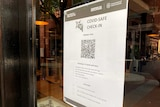 A QR code printed out on a page and stuck to a glass window