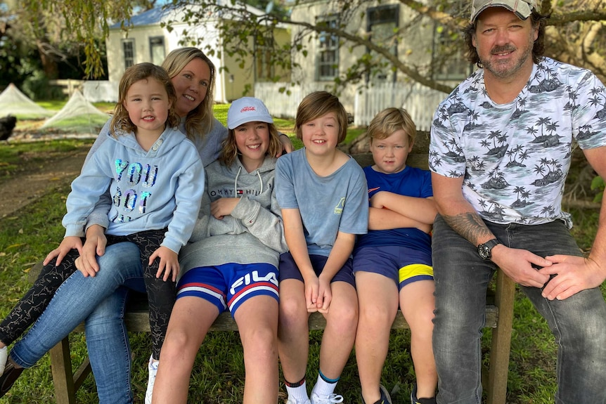 A family sit on a chair in country Victoria