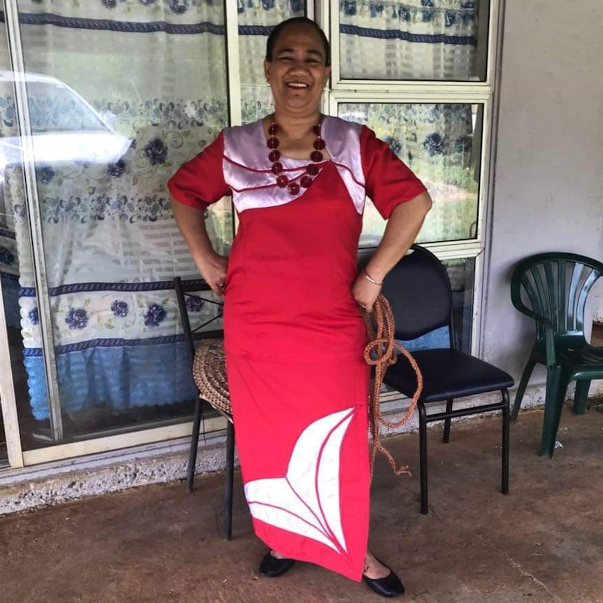 A woman in a red dress stands and smiles with her hands on her hips.