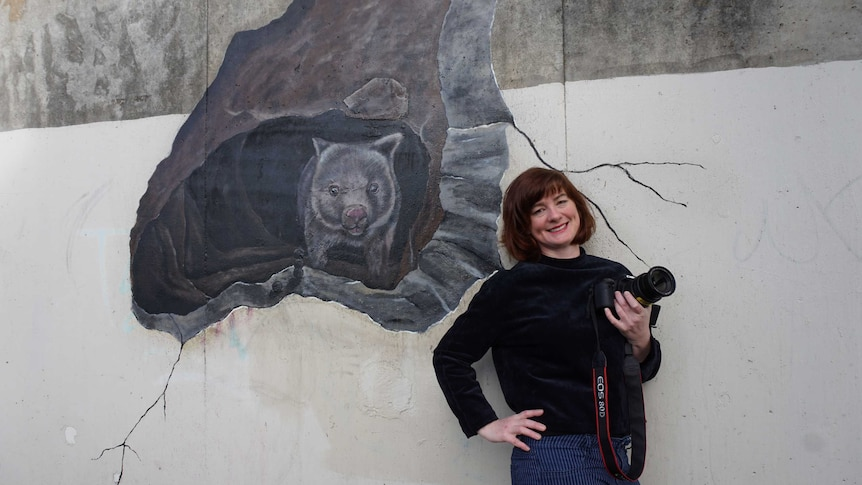 Bissland holding camera smiling and leaning against wombat mural.