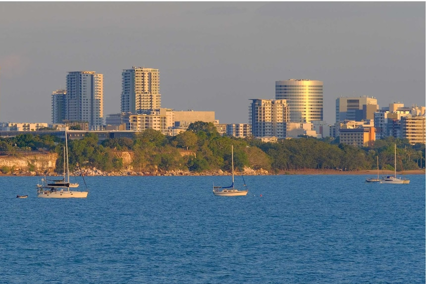 A view of the city from the sea with sunset light reflecting off the high-rise. Yachts are moored in the foreground.
