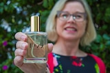 Ally Martell holds a bottle of perfume.