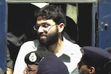 Ahmed Omar Saeed Sheikh stands near police at the front of a court.