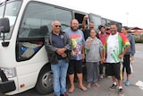 Eight Indigenous locals from Wilcannia stand in front of a bus