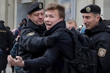 A man exclaims as he is detained by black-clad police officers