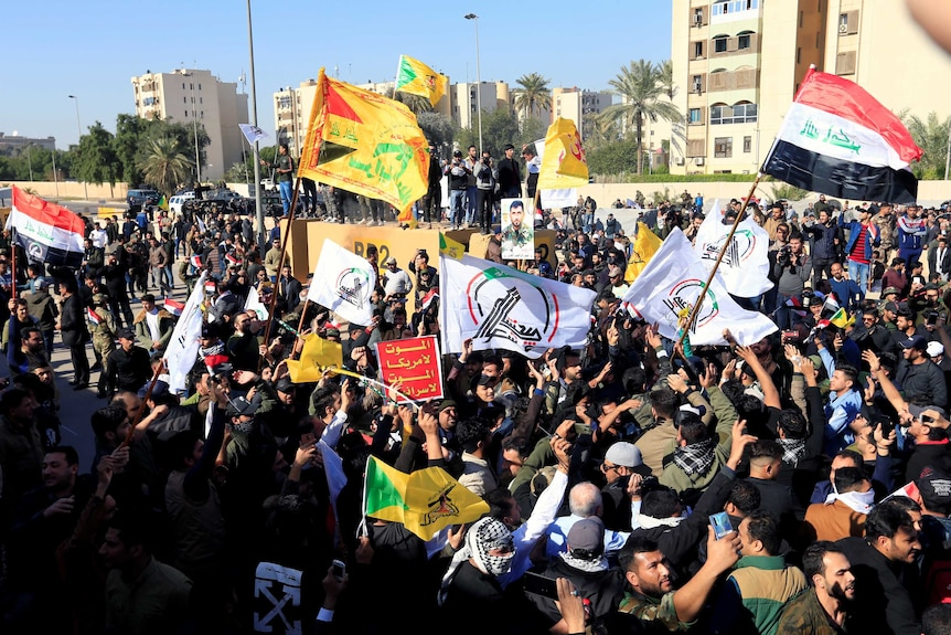 A large group of protesters and militia fighters wave Iraqi flags among other flags.