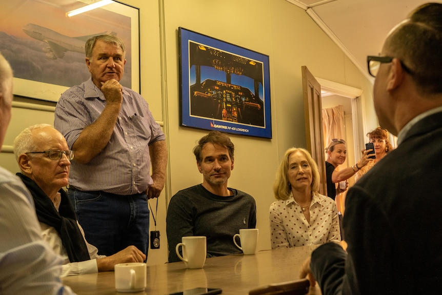 A standing man presents to a group of people sitting around a table, with airline memorabilia on the walls behind him.