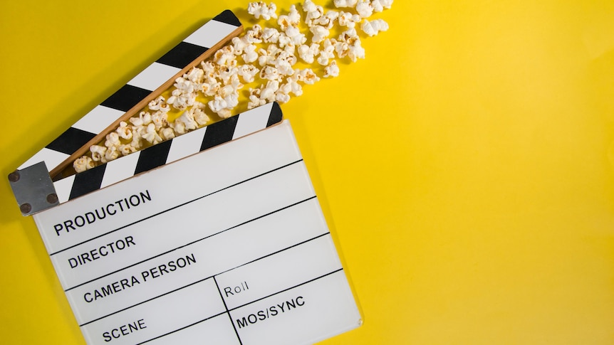 Popcorn coming out of a clapperboard on a yellow background.