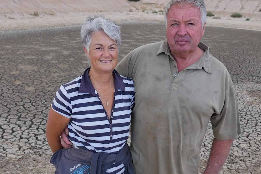 A couple stand in front of a dry and empty dam on a farm.