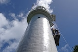 photo looking up at the lighthouse with painter hanging off side
