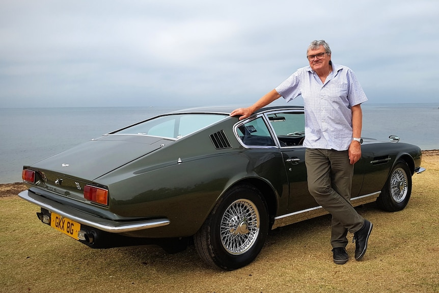 An older man leans against an olive green sports car