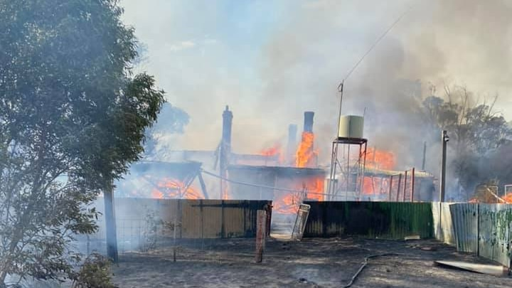 A photo of a homestead on fire with a nearby water tank and trees.