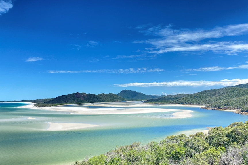 A beach surrounding by hills and pure white sand swirling into the ocean