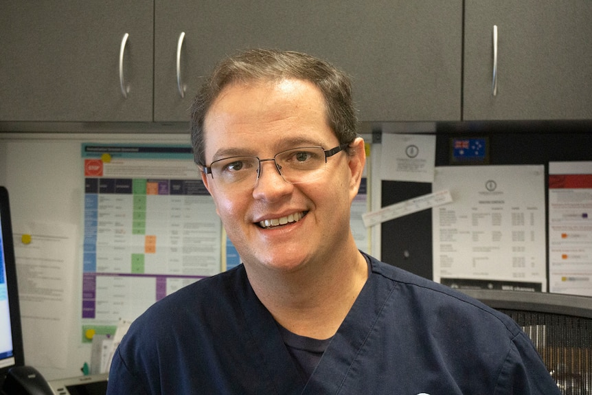 A male doctor sitting in a chair and smiling at the camera. He wears glasses and a dark blue uniform.