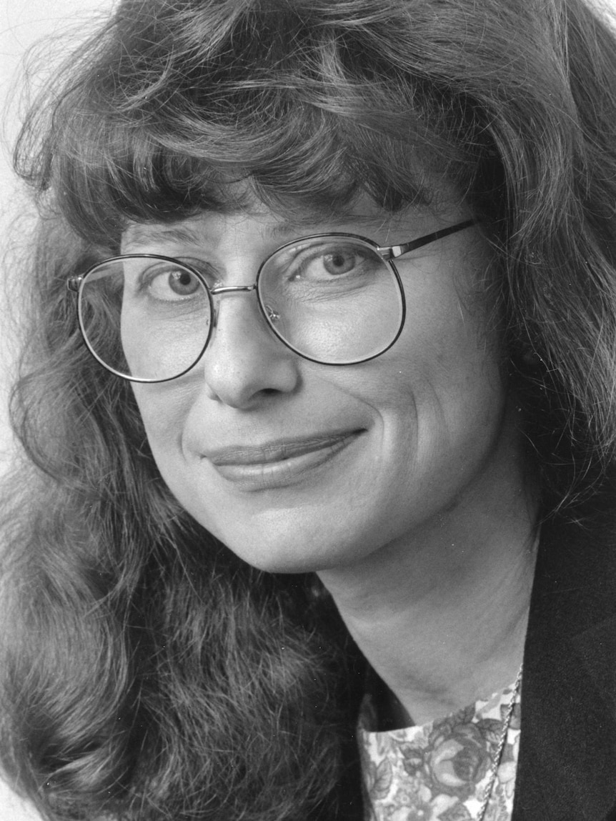 Black and white portrait shot of Kohn wearing round glasses with long wavy hair.