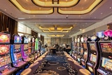 Gaming machines inside Crown Perth's Pearl Room, with gaming tables and casino staff in the background.