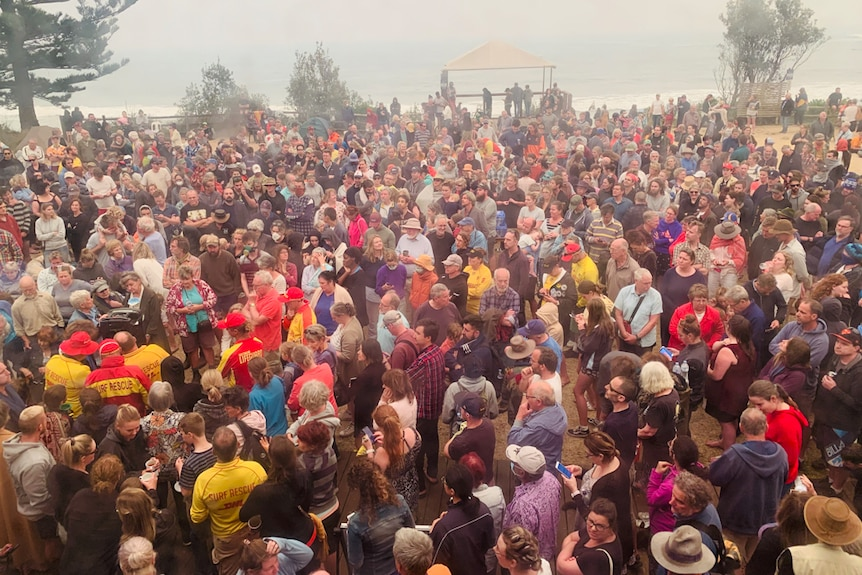 Large crowd gathered with beach in background