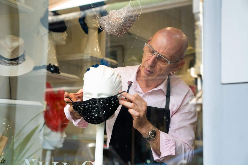 a tailor at a window shop putting a mask over a mannequin head