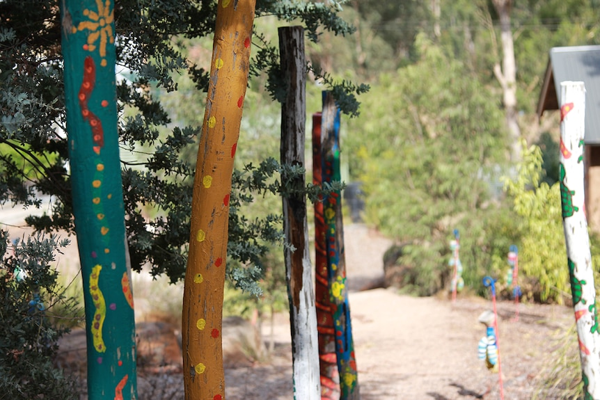 Colourful painted poles in a bush garden.