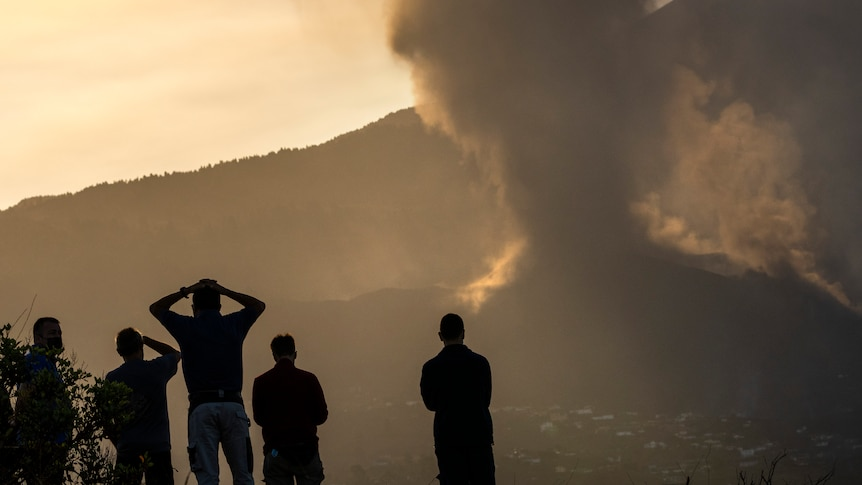 Residents look from a hill as lava continues to flow