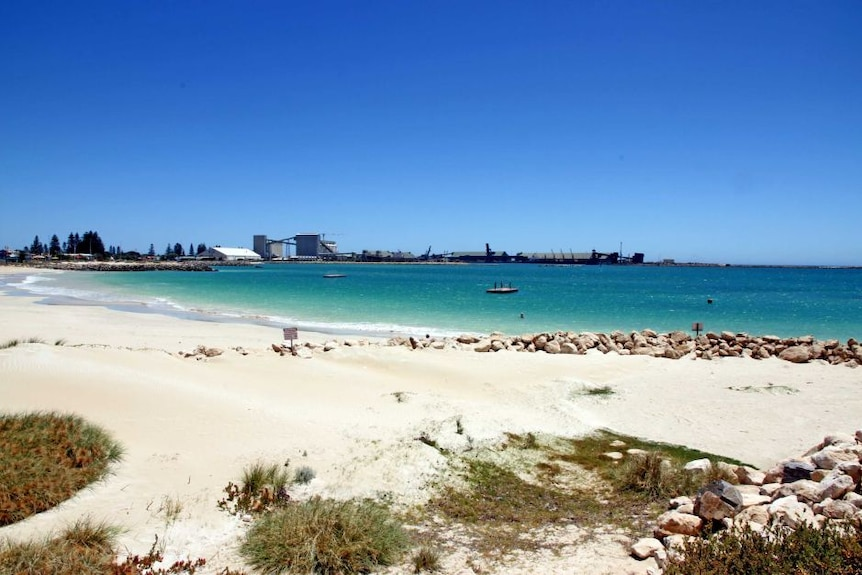 A landscape shot of the beach in Geraldton, white sand fades to crystal blue water. The port can be seen in the background.