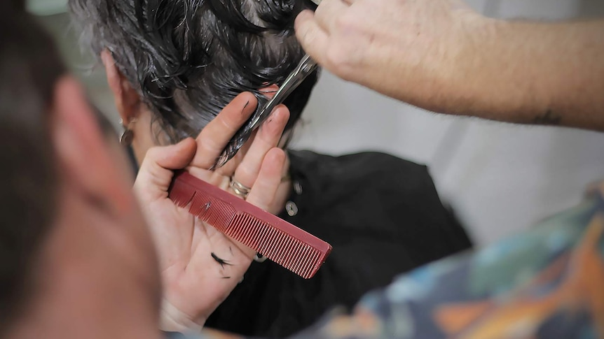 Close up of a male hairdresser cutting a woman's hair with a comb and scissors