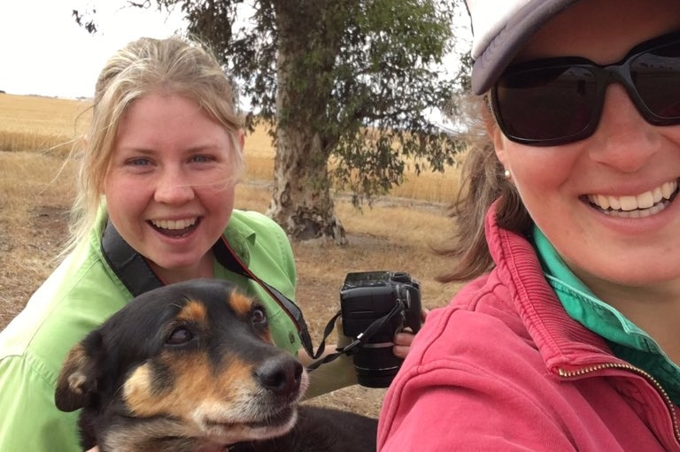 two girls smile on a farm with a dog