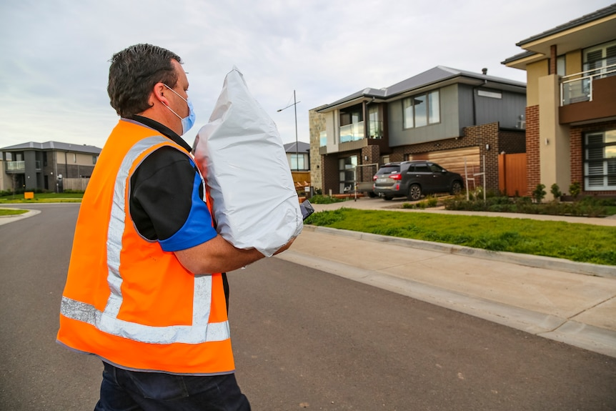 A man in an orange high-vis vest carries a large package as he crosses a suburban street.