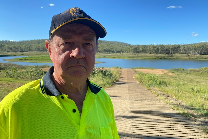 A frowning man with a cap and a yellow high-visibility shirt standing outside, with green foliage behind him and a very low dam