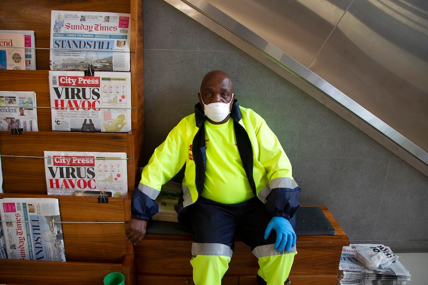 A man in bright hi-vis yellow clothing stares into the camera sitting next to a newspaper stand in front of an escalator.