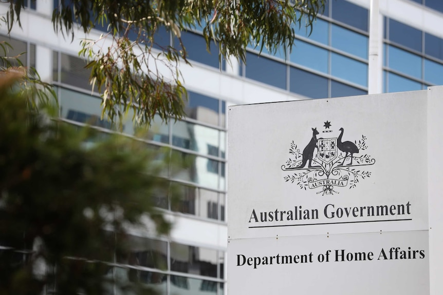 "A sign saying ""Australian Government Department of Home Affairs"" outside a tall building. There are leaves in the foreground"